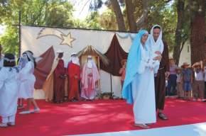 El pesebre de Belén con los reyes magos y pastorcitos atrás, adelante María sostiene al Niño Jesús y a su lado José