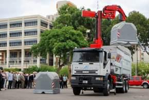 El camión robotizado levanta un container de basura