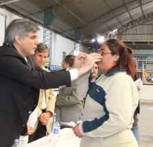 El ministro de Desarrollo Humano, Daniel Molina entrega sus anteojos a una persona que fue censada en el operativo realizado meses atrás